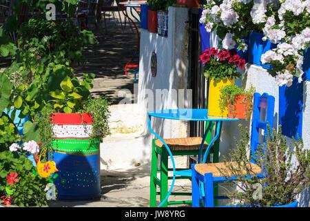 Bunte handgemachte Gartenmöbel Aufenthalt unter Blume und grüne Vegetation - Stockfoto