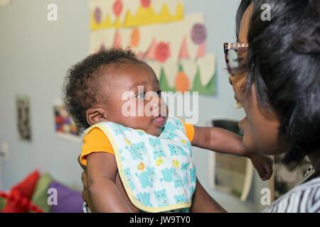 Charlotte, North Carolina - ein Baby mit einem Lehrer im Kopf Beginnen am Bethlehem Center. Das Zentrum dient Familien - Stockfoto