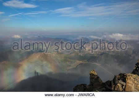 Eine Ansicht mit Schatten von zwei Menschen, ein Regenbogen und Berg Gespenst in Lagorei von der Cima d'Asta. - Stockfoto