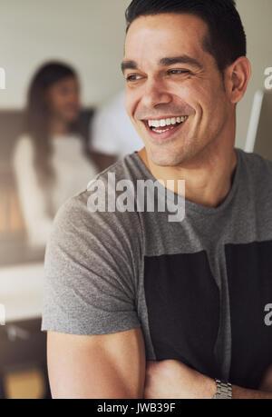 Vertikale Portrait von einem Geschäftsmann, der mit verschränkten Armen und Wegsehen im Büro. - Stockfoto