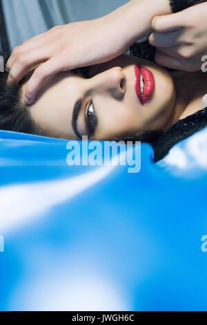 Schöne junge Frau zur Festlegung im Bett verstecken Gesicht mit den Händen - Stockfoto