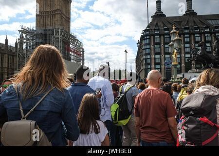 London, Großbritannien, 12. August 2017. Massen von Touristen auf die Westminster Bridge auf einem bedeckt, aber - Stockfoto