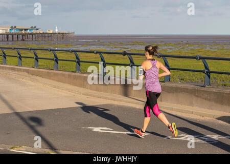 Southport, Merseyside. UK Wetter. August 13, 2017. Hellen sonnigen Start in den Tag als Jogger die wärmenden Sonnenstrahlen - Stockfoto