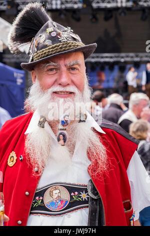 Typisch Bayerische Zeichen in der traditionellen Tracht der Lederhosen, Westen, Hüte mit Federn, Blumen, Emaille - Stockfoto
