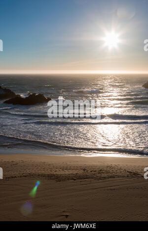 Sonnenuntergang über glatten Sandstrand mit Felsen im Ozean - Stockfoto