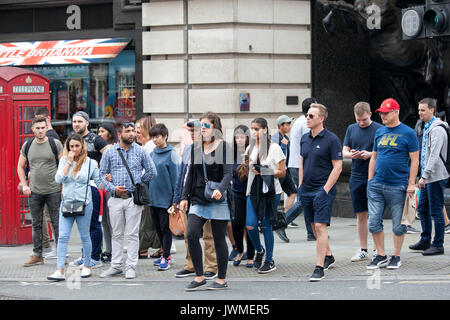 LONDON, ENGLAND - 11. August 2017 Menschen warten auf das grüne Licht zu drehen, um die Straße zu überqueren, in - Stockfoto
