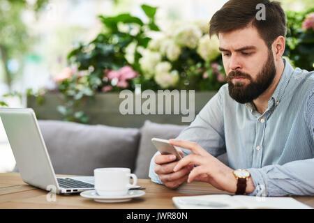 Portrait des modernen bärtiger Mann mit Smartphone, während mit Laptop am Tisch in gemütlicher Café Lounge im Freien - Stockfoto