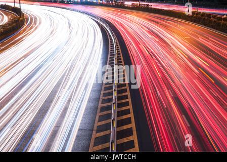 Autos leichte Wanderwege auf einer gekrümmten Autobahn Straße in der Nacht in Chengdu City - Stockfoto