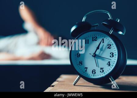 Schlafstörungen oder Schlaflosigkeit Konzept, selektiver Fokus der vintage Uhr in Schlafzimmer und unscharf, männliche - Stockfoto