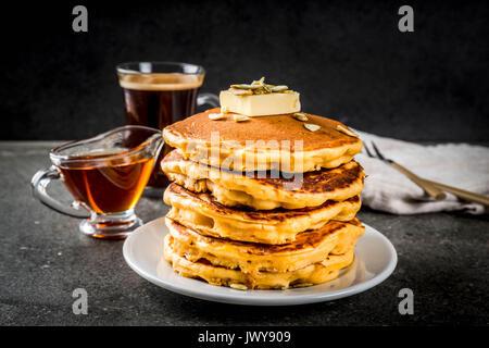 Herbstliche traditionelles Essen. Stapel von Kürbis Pfannkuchen mit Butter, Kürbiskerne und Ahornsirup. Mit einer Tasse Kaffee. Auf einem schwarzen Steintisch. Kopieren Sie sp