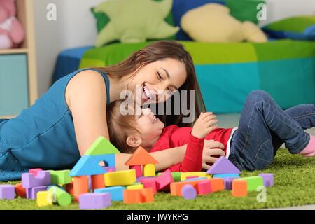 Mutter oder Kindermädchen spielen mit einem Kind auf dem Teppich in einem Zimmer zu Hause - Stockfoto