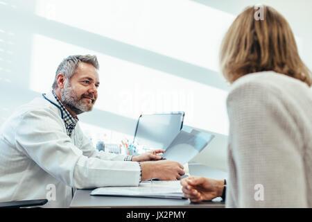 Männlicher Arzt in Kommunikation mit weiblichen Patienten. Facharzt im Gespräch mit weiblichen Patienten während - Stockfoto