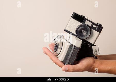 Nahaufnahme von einem jungen Mann mit einem Stapel von alten Film Kameras in seine Hände, gegen einen weißen Hintergrund - Stockfoto