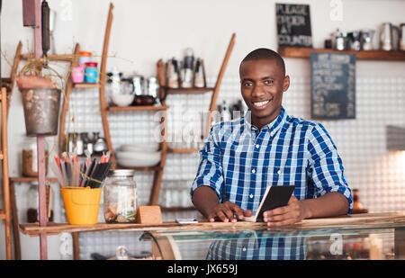 Lächelnden jungen afrikanischen Unternehmer in seinem Cafe arbeiten - Stockfoto