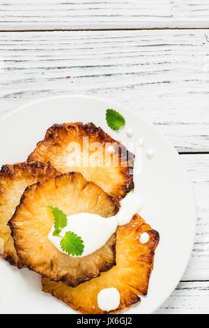 Gebratene Ananasscheiben mit Creme fraiche, Minze in Weiß Platte auf Holz- Hintergrund. Ansicht von oben - Stockfoto