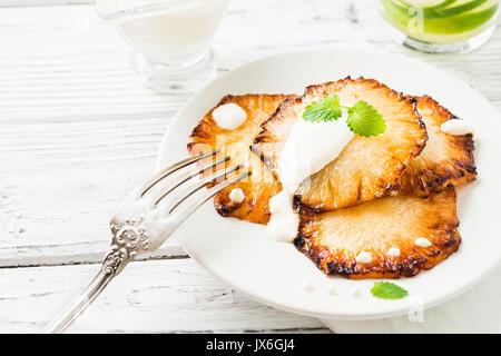 Gebratene Ananasscheiben mit Creme fraiche, Minze in Weiß Platte auf Holz- Hintergrund - Stockfoto