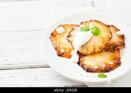 Gebratene Ananasscheiben mit Creme fraiche, Minze in Weiß Platte auf Holz- Hintergrund. Platz kopieren - Stockfoto