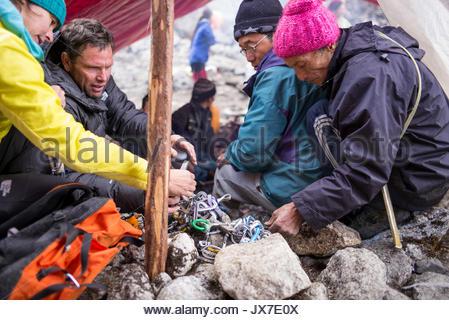 Expeditionsteilnehmer prüfen Geräte mit Hilfe von lokalen Guides. - Stockfoto