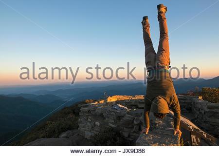 Ein Mann führt einen handstand an der Spitze der schroffen Pinnacle Wanderweg entlang des Blue Ridge Parkway. - Stockfoto