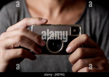 Nahaufnahme eines jungen kaukasischen Mann mit einem retro Film Kamera - Stockfoto