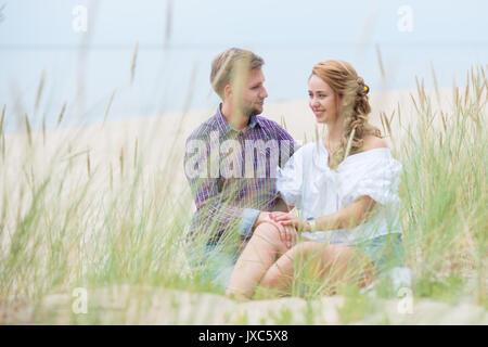 Junge Familie Paar Picknick am Strand in der Nähe des Meeres, Tee trinken und entspannen in der Hängematte im Sommer - Stockfoto