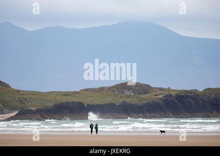 Ein paar wenige ihren Hund Rhosneigr Strand mit llanddwyn Island oder Ynys Llanddwyn hinter Ihnen und Snowdonia - Stockfoto