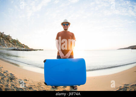 Mann in Sonnenbrille mit Gepäck auf dem Meer im Sommer sonnigen Tag. - Stockfoto