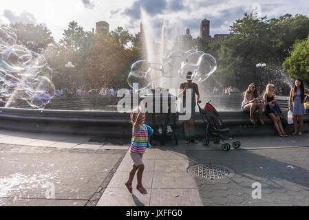 New York, NY, USA - 13. August 2017 - Ein junges Mädchen jagt ein Spray von Bubble Spray an einem heissen Sommertag - Stockfoto