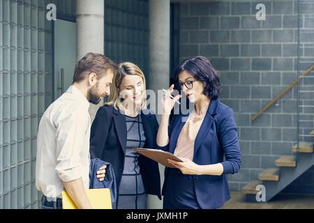 Unternehmer und Frauen diskutieren Schreibarbeit in Großraumbüro - Stockfoto