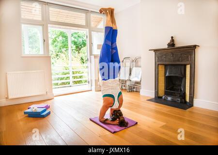 Auf dem Kopf stehende Frau in Yoga Position - Stockfoto