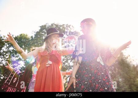 Zwei junge boho Frauen tanzen im Sonnenlicht bei Festival - Stockfoto