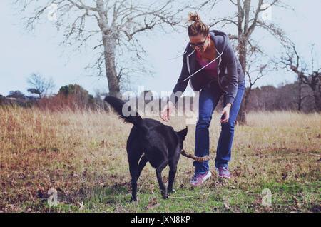 Frau spielen Fetch mit Hund in Weide, authentische aktive Familie Lebensstil mit dem Tier. - Stockfoto