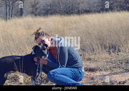 Mädchen und Fell Baby spielen in das Feld ein. Annahme durch den schwarzen und weißen Hund empfängt Umarmen und - Stockfoto