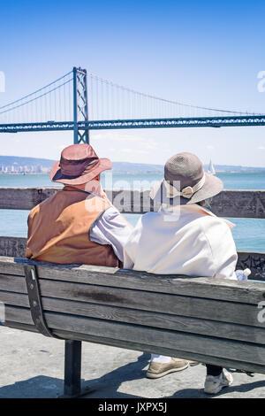San Francisco senior Paar am Ferry Building sitzen und einen Blick auf die Bay Bridge. Von der Rückseite aus betrachtet. - Stockfoto