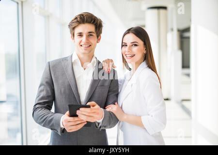 Zwei lächelnde elegante Business Leute Mann in Anzug und Frau in Jacke und Kleid suchen auf digitalen Tablet im - Stockfoto