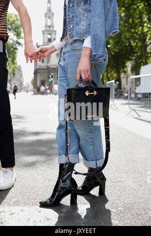 Frau in Denim mit hand Handtasche holding Mann, niedrige Abschnitt - Stockfoto