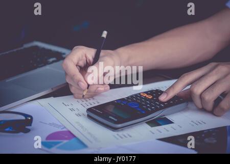 Nahaufnahme, Geschäftsmann, Hand, Smartphone und Finanzen und auf Holz- Tabelle über die Kosten zu Hause Büro berechnen. - Stockfoto