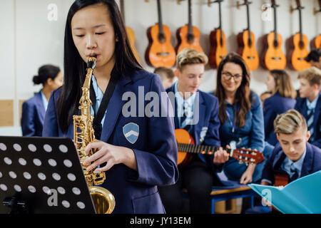 Teen student spielt das Saxophon in ihrer Schule Musik Lektion. Der Rest der Klasse sind im Hintergrund, unscharf. Stockfoto