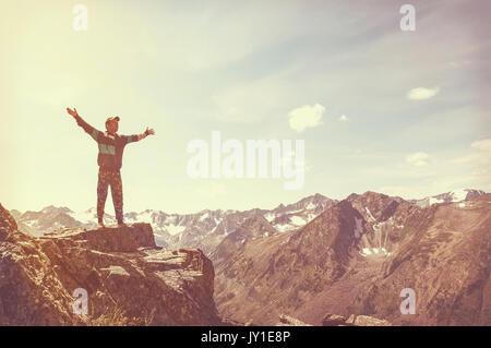 Kletterpflanze erreicht seine Arme, stehend auf einem Stein an der Oberseite seiner Route, über einem tiefblauen - Stockfoto