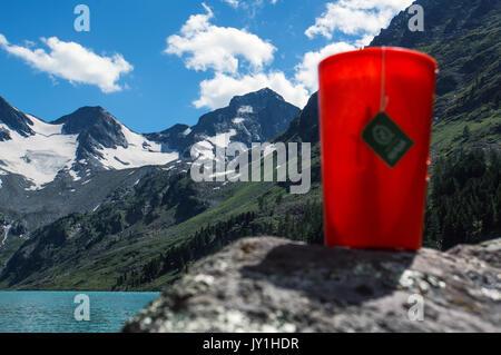 Tasse Tee. Warmes Getränk in den Bergen im Hintergrund, See und Berge mit Bäumen auf der Piste. Picknick im Wald - Stockfoto