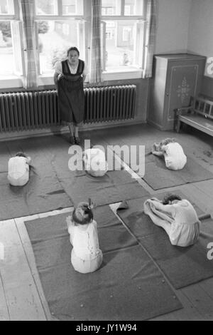 Gruppe von kleinen Mädchen ihre Zehen berühren im Sportunterricht der Klasse. - Stockfoto
