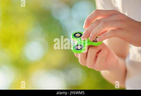 Teenager auf dem weißen t-shirt Hand beliebte Antistress zappeln Spinner. Mann spielt mit grünen Spinner im Freien - Stockfoto