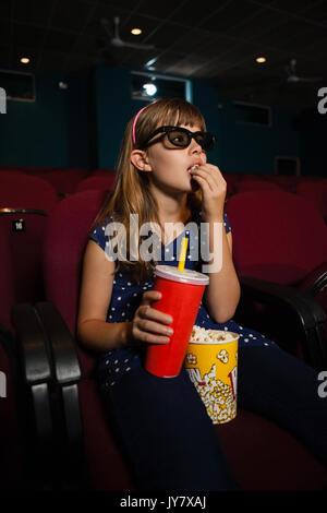 Mädchen mit 3D-Brille beim Essen Popcorn während der Film im Theater - Stockfoto