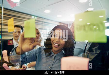 Lächeln, Geschäftsfrau, Haftnotiz auf Glas, Gruppe von Kollegen hinter ihr - Stockfoto