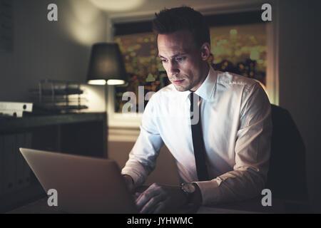 Nachdenklich Geschäftsmann Eingabe beim Sitzen am Laptop im Büro in der Nacht. - Stockfoto