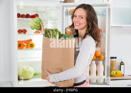 Happy Woman Holding Einkaufen Tasche mit Gemüse vor dem offenen Kühlschrank - Stockfoto