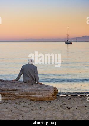 Ein grauhaariger Mann in einem beige Jacke auf Treibholz an der Segelboote auf dem Meer bei Sonnenuntergang sitzen. - Stockfoto
