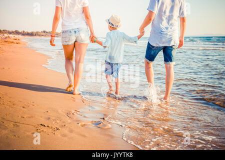Rückansicht des blonden Jungen Familie zu Fuß am Strand. - Stockfoto