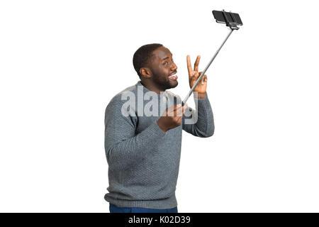 Fröhliche schwarzer Mann unter selfie. Studio shot der Jungen glücklich Schwarz afro-amerikanische Mann lächelnd - Stockfoto