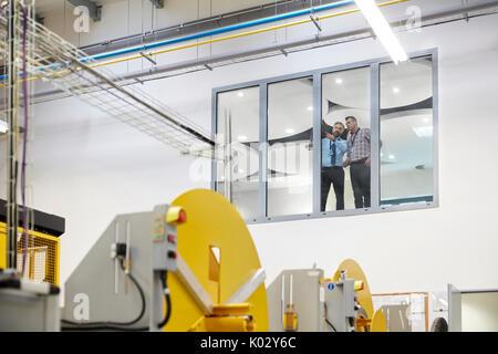 Männlichen Vorgesetzten sprechen am Fenster oben Fabrik - Stockfoto